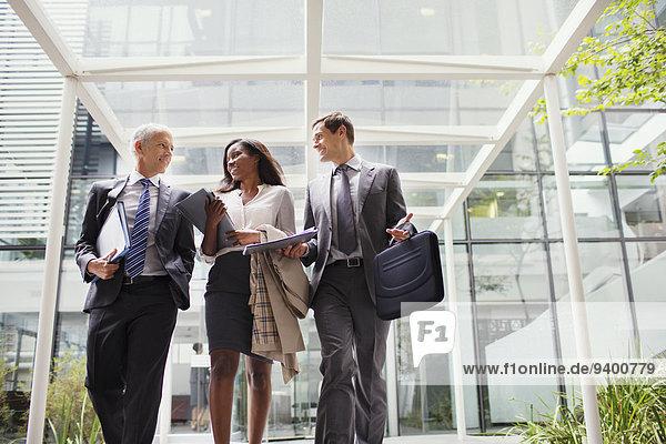 Geschäftsleute  die zusammen aus dem Bürogebäude gehen.