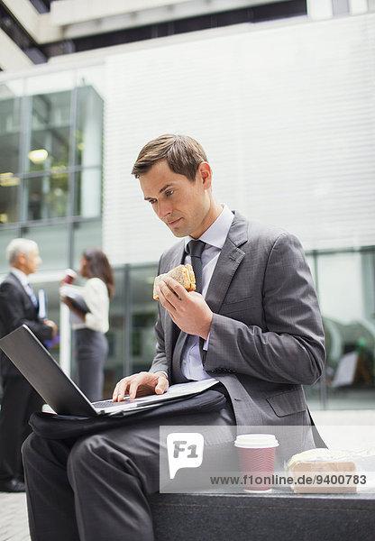 Geschäftsmann isst zu Mittag und arbeitet außerhalb des Bürogebäudes