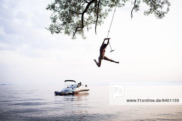 junge Frau junge Frauen schaukeln schaukelnd schaukelt schwingen schwingt schwingend Seil Tau Strick Boot Schaukel
