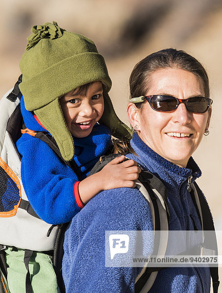 2-3 Years 40-44 Years Baby Carrier Boys California Cap Carrying Childhood day Enjoyment Family With One Child Focus On Foreground Fun Happiness Hiking Laughing Mature Adult Mature Women mother One Parent outdoors portrait Preschool Child Son Sports Clothi