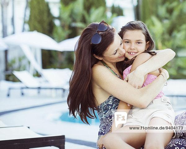 Mutter umarmt ihre Tochter am Pool