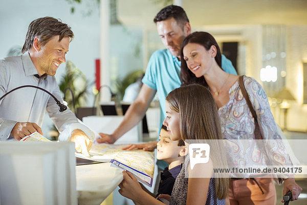 Familie mit zwei Kindern an der Rezeption in der Hotellobby