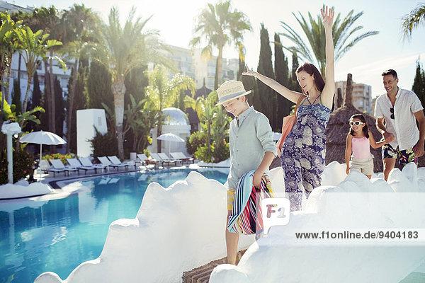 Glückliche Familie mit zwei Kindern  die am Schwimmbad spazieren gehen