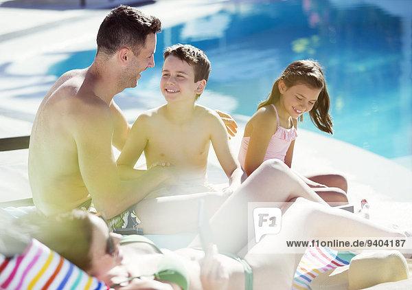 Familie mit zwei Kindern am Schwimmbad