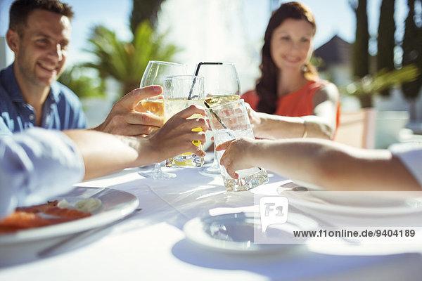 Freunde  die bei Tisch im Freien anstoßen