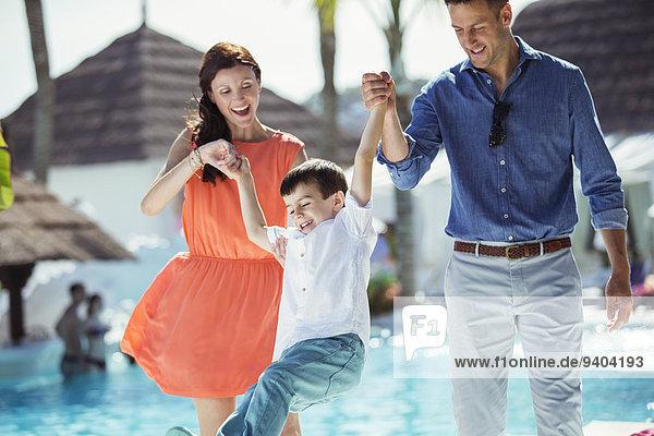 Kleiner Junge amüsiert sich mit seinen Eltern am Swimmingpool