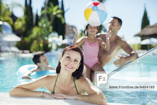 Porträt der lächelnden Frau im Schwimmbad  Familienspiel mit Strandball im Hintergrund