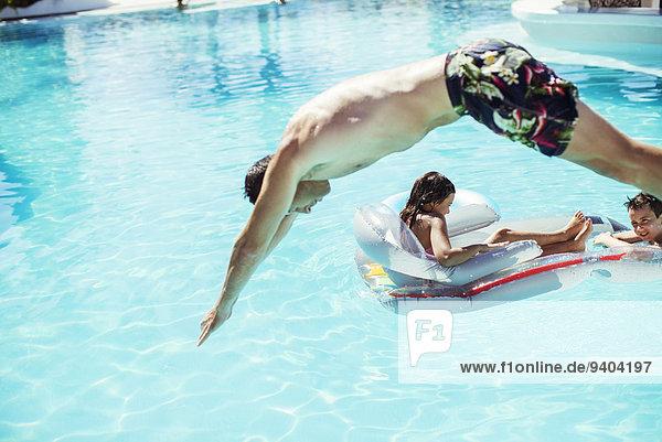 Mann taucht ins Schwimmbad  Kinder schwimmen auf Luftmatratze im Hintergrund