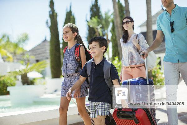 Familie mit Koffern zu Fuß in Richtung Ferienort