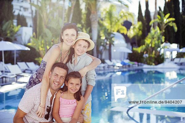 Porträt der glücklichen Familie mit Sohn und Tochter am Schwimmbad