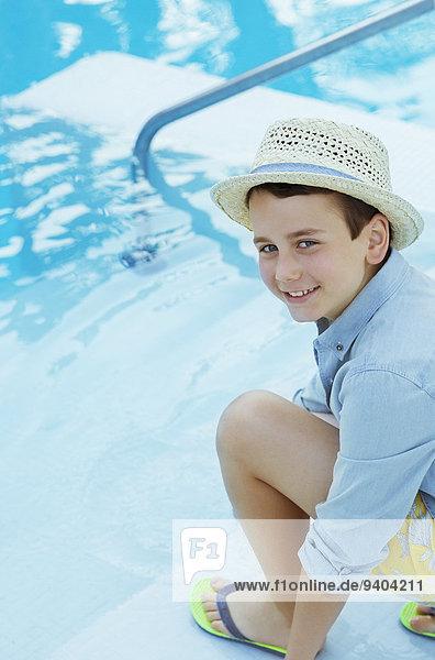 Porträt eines lächelnden Jungen mit Strohhut  der am Swimmingpool hockt