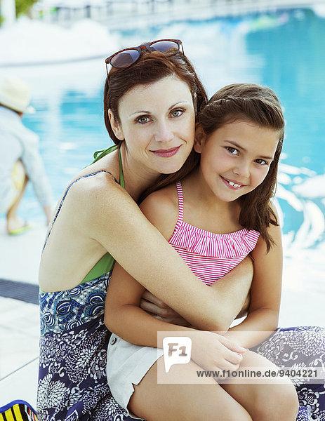 Porträt von Mutter und Tochter am Pool sitzend