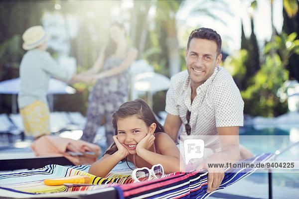 Porträt eines lächelnden Vaters und einer lächelnden Tochter am Schwimmbad  Mutter und Tochter im Hintergrund