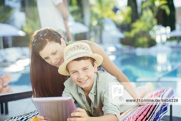 Mutter und Sohn mit Tablet PC am Schwimmbad
