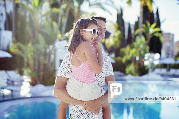 Mann trägt seine Tochter am Swimmingpool