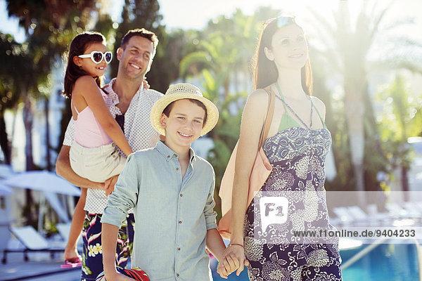 Familie mit zwei Kindern zu Fuß durch das Resort Schwimmbad