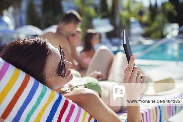 Frau beim Sonnenbaden und Texten am Schwimmbad