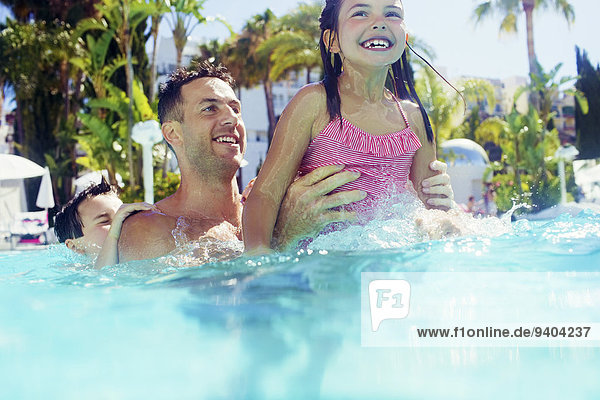 Vater mit Tochter und Sohn beim Spielen im Schwimmbad