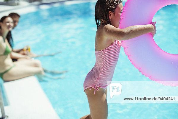 Mädchen mit rosa aufblasbarem Ring beim Sprung ins Schwimmbad