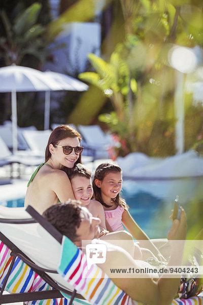 Familie mit zwei Kindern beim Sonnenbaden am Kurschwimmbad