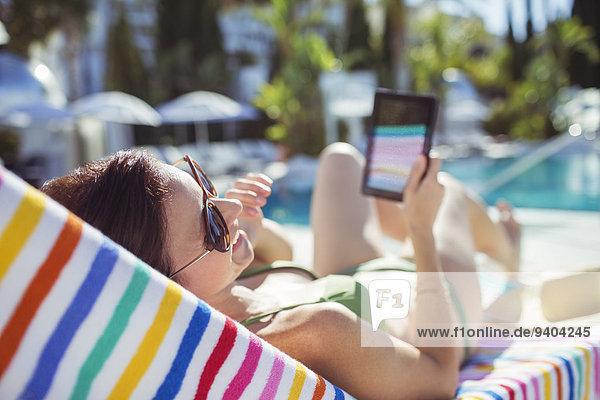 Lächelnde Frau mit digitalem Tablett zum Sonnenbaden am Schwimmbad