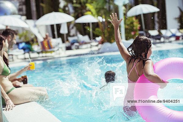 Mädchen mit rosa aufblasbarem Ring beim Sprung ins Schwimmbad  Familie im Hintergrund