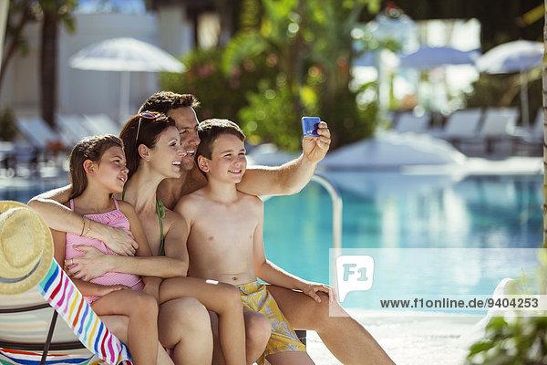 Familie mit zwei Kindern  die Selfie im Schwimmbad nehmen