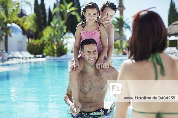 Vater beim Huckepackfahren seiner beiden Kinder im Schwimmbad