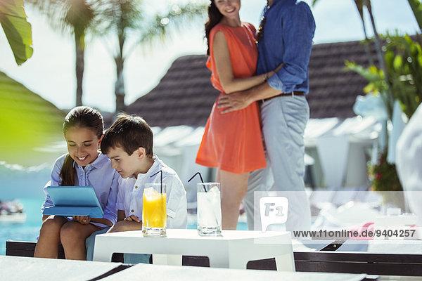 Geschwister mit digitalem Tablett im Schwimmbad  die Eltern im Hintergrund
