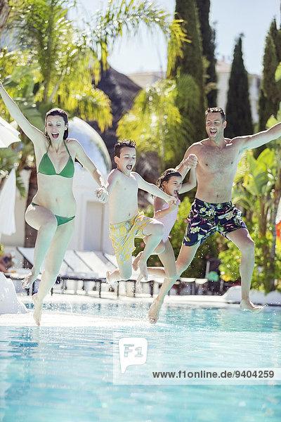 Familie mit Sohn und Tochter  die Händchen halten und ins Schwimmbad springen.