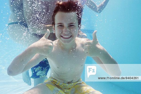 Portrait des Jungen mit Daumen nach oben unter Wasser  Person im Hintergrund