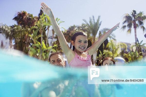 Eltern mit Tochter beim Spielen im Schwimmbad
