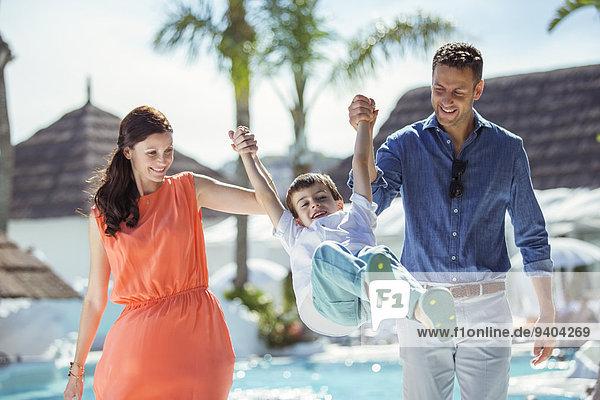 Junge hält Händchen mit seinen Eltern am Swimmingpool