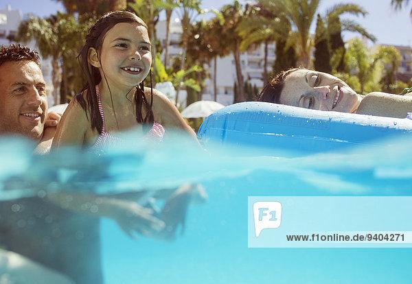 Mädchen schwimmen mit ihren Eltern im Schwimmbad