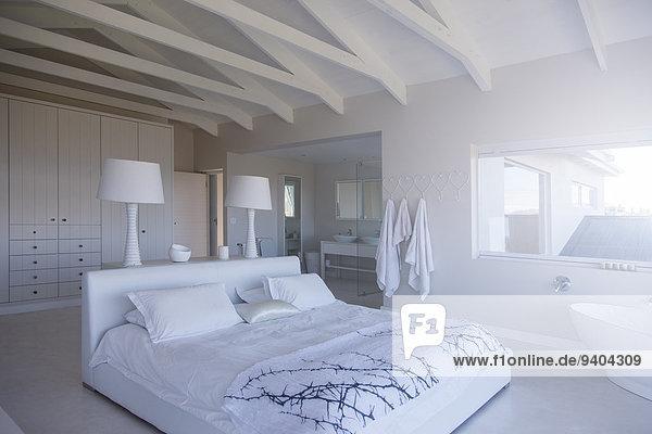 Modernes weißes Schlafzimmer mit Doppelbett und Badewanne