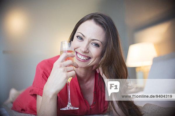 Porträt einer lächelnden Frau auf dem Bett liegend mit Champagnerflöte