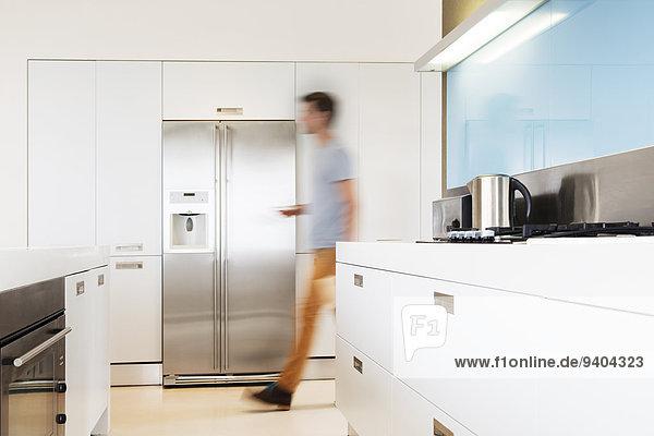 Ein Mann  der in seiner modernen Küche auf den Kühlschrank zugeht.