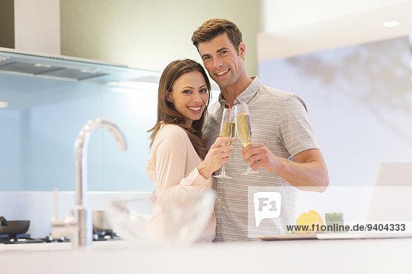 Porträt eines lächelnden Paares  das mit Champagnerflöte in der Küche anstößt.