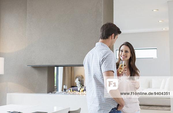 Lächelndes Paar beim Toast mit Champagnerflöten im Wohnzimmer