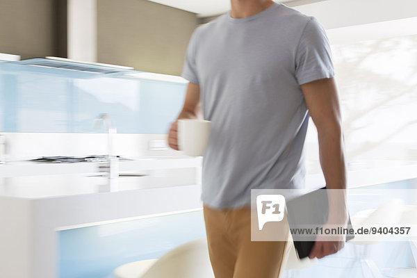Mann mit Kaffeetasse und digitalem Tablett durch die moderne Küche gehend