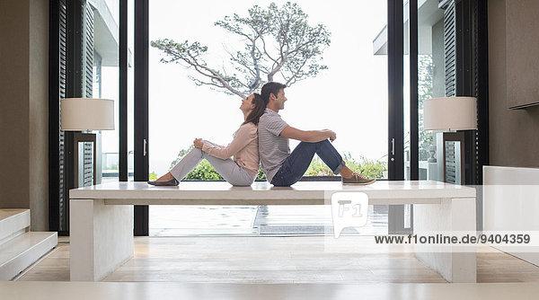 Paar sitzt Rücken an Rücken auf dem Tisch