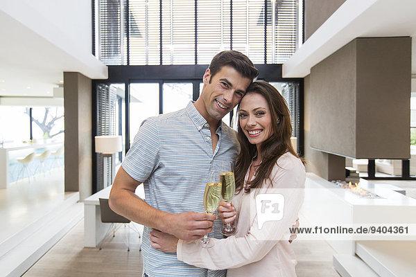 Porträt eines lächelnden Paares  das Champagnerflöten im modernen Wohnzimmer umarmt und hält.