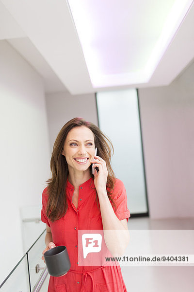 Lächelnde Frau in rotem Kleid  die im Hausflur telefoniert.