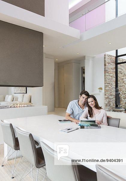 Porträt eines Paares im Esszimmer mit Büchern  Zeitung und digitalem Tablett auf dem Tisch