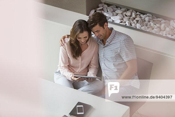 Paar mit Tablet PC im Esszimmer