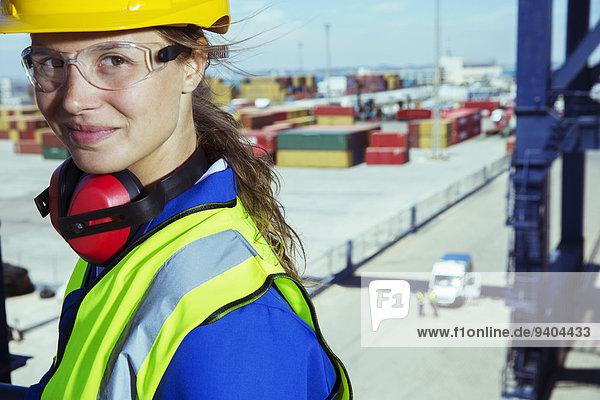 Arbeiter lächelt in der Nähe von Frachtcontainern