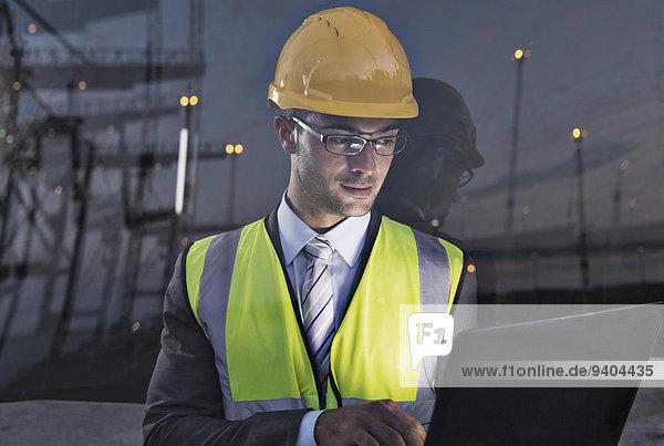 Geschäftsmann in Arbeitsschutzbekleidung in Fensternähe