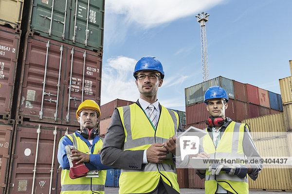 Geschäftsleute in Arbeitsschutzbekleidung in der Nähe von Frachtcontainern
