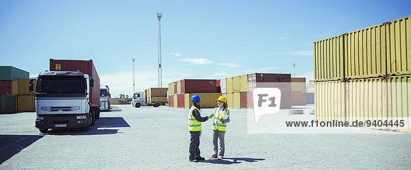 Arbeiter reden in der Nähe von Frachtcontainern