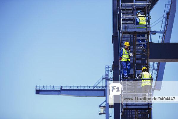 Arbeiter klettern auf den Ladekran